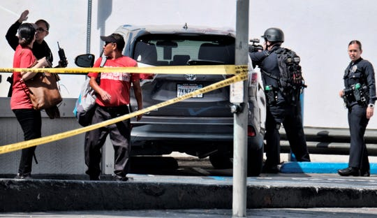 An Los Angeles police offer directs Jack in the Box employees from the restaurant after a shooting in Van Nuys on Thursday. Police say a male teenage student and a female school employee were wounded.