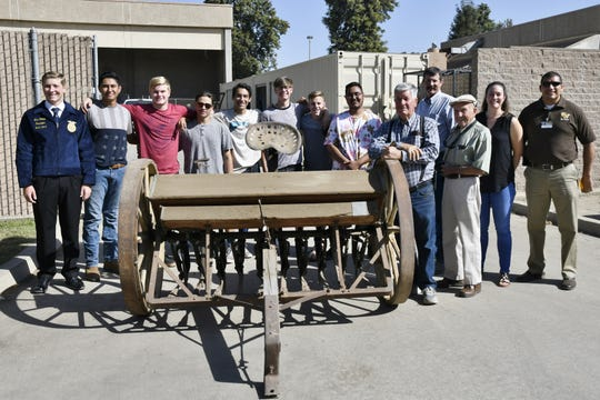 Golden West students, administrators and members of the Tulare County Historical Society pose for a photo with an antique grain drill set to be restored on Friday, September 21, 2018.