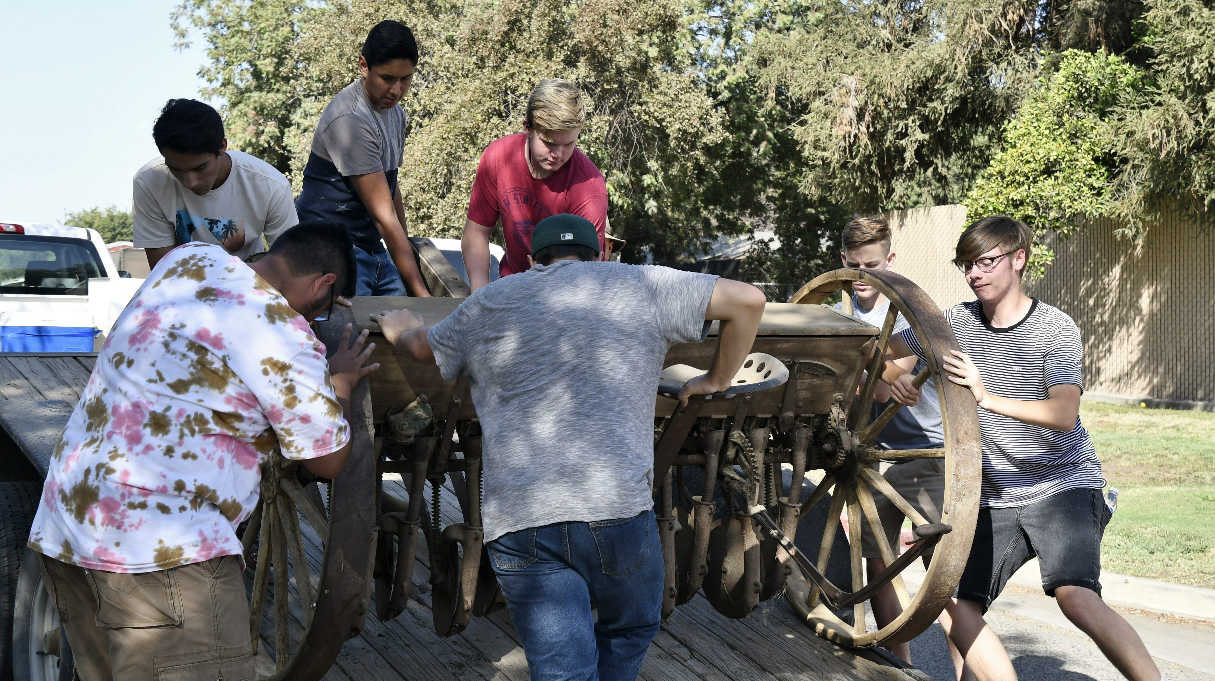 Golden West Ag mechanic students unload an antique grain drill on Friday, September 21, 2018.