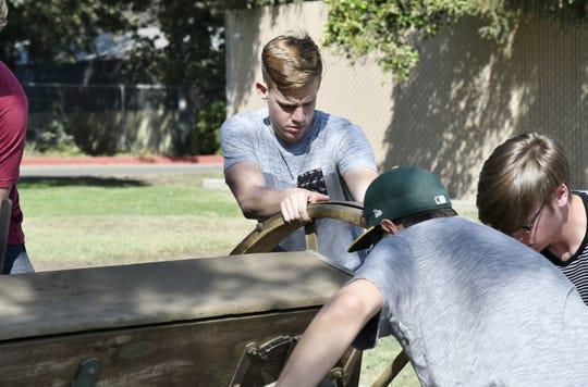 Golden West student Dawson Dolan helps unload an antique grain drill on Friday, September 21, 2018.