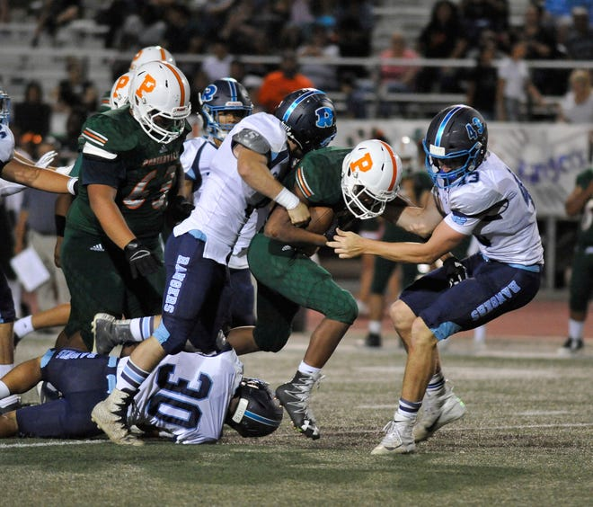 Porterville Isaiah Ellis gets pulled down by Redwood in a non-league game at Jacob Rankin Field in Porterville on September 20, 2018.