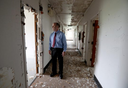 Stony Point Supervisor Jim Monaghan looks into a room in Wilbur Hall, one of the long boarded up, decrepit buildings on the campus of Letchworth Village in Stony Point Sept. 21, 2018. Monaghan gave an update on the status of plans to develop the site. The plans would include knocking down several of the boarded up buildings, including Wilbur Hall.