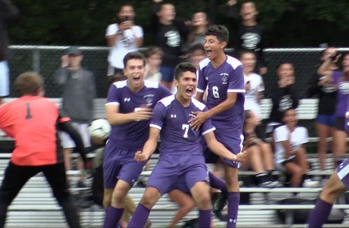 New Rochelle's Johan Velez  (7) celebrates with teammates after his game winning goal in overtime against Mamaroneck in boys soccer action at City Park in New Rochelle Sept. 20, 2018. New Rochelle won the game 2-1.