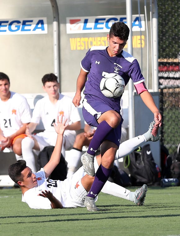 New Rochelle's Johan Velez  (7) moves the ball away from Mamaroneck's Joseph Lopez during first half action at City Park in New Rochelle Sept. 20, 2018. New Rochelle won the game 2-1 with Velez scoring the game winning goal in overtime.