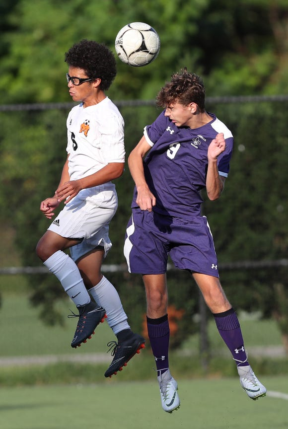 From left, Mamaroneck's Angel Martinez (6) and New Rochelle's Connor Burke (9) battle for ball control during boys soccer acton at City Park in New Rochelle Sept. 20, 2018. New Rochelle won the game 2-1 in overtime.