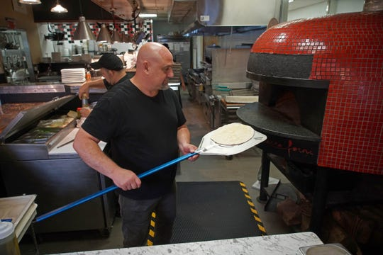 Culinary consultant Ciro Verdi, for the Touch of Italy, a Sussex County Italian chain, prepares one of his specialty items focaccia robiola in a brick oven at the new Touch of Italy location on Rt. 202.