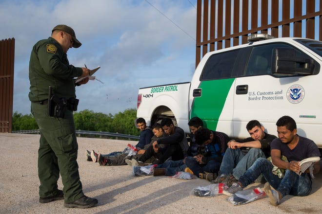 In this file photo taken on March 26, 2018, a Border Patrol agent apprehends illegal immigrants shortly after they crossed the border from Mexico into the United States in the Rio Grande Valley Sector near McAllen, Texas.