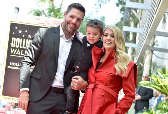 Carrie Underwood, Mike Fisher and Isaiah Michael Fisher attend her Walk of Fame ceremony.