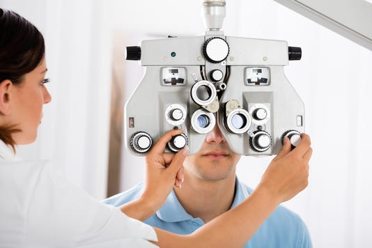 Female Optometrist Adjusting Phoropter For Patient