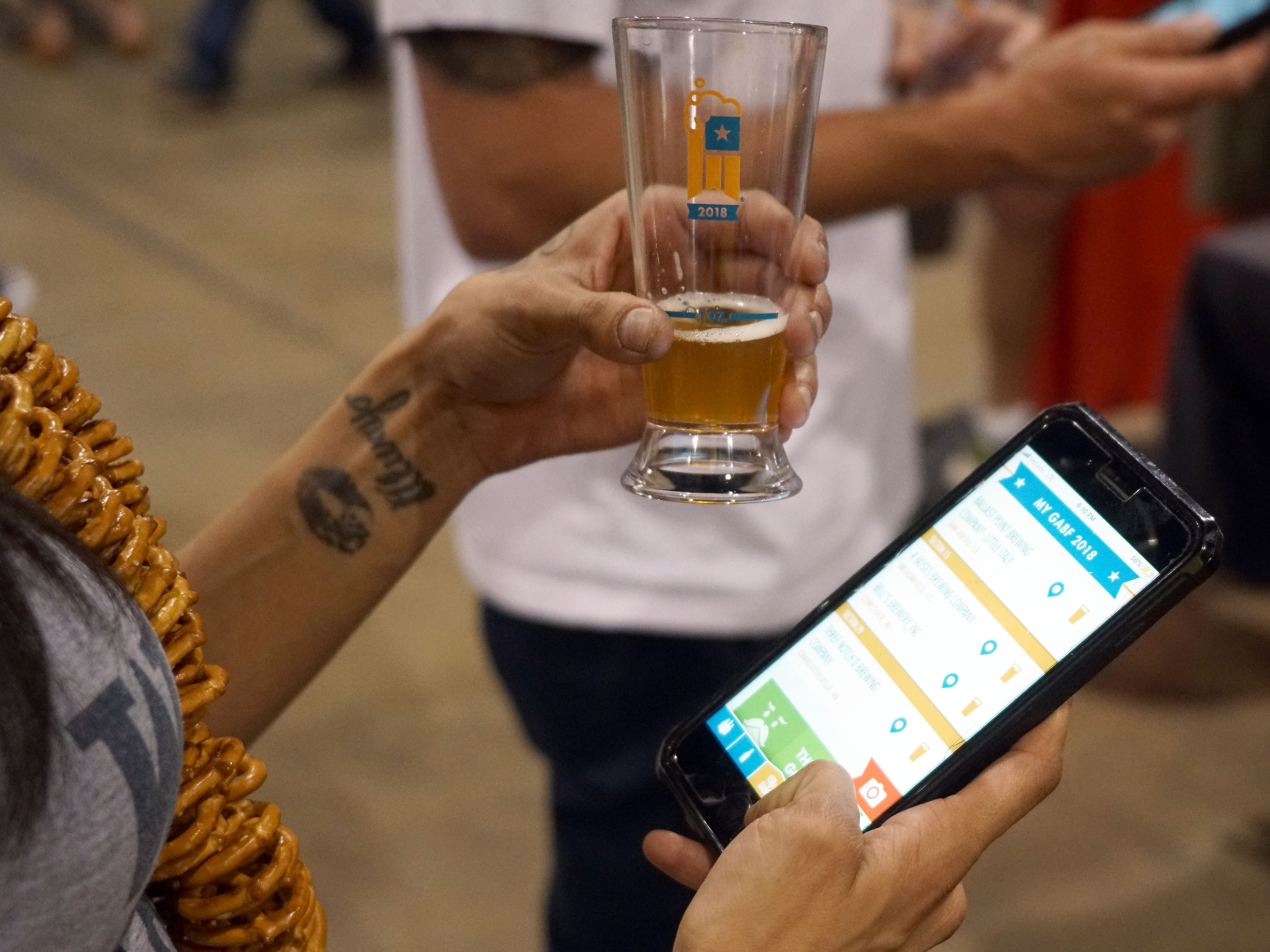 A patron at the Great American Beer Festival holds a taster of beer while she uses the GABF app to plot her next move.