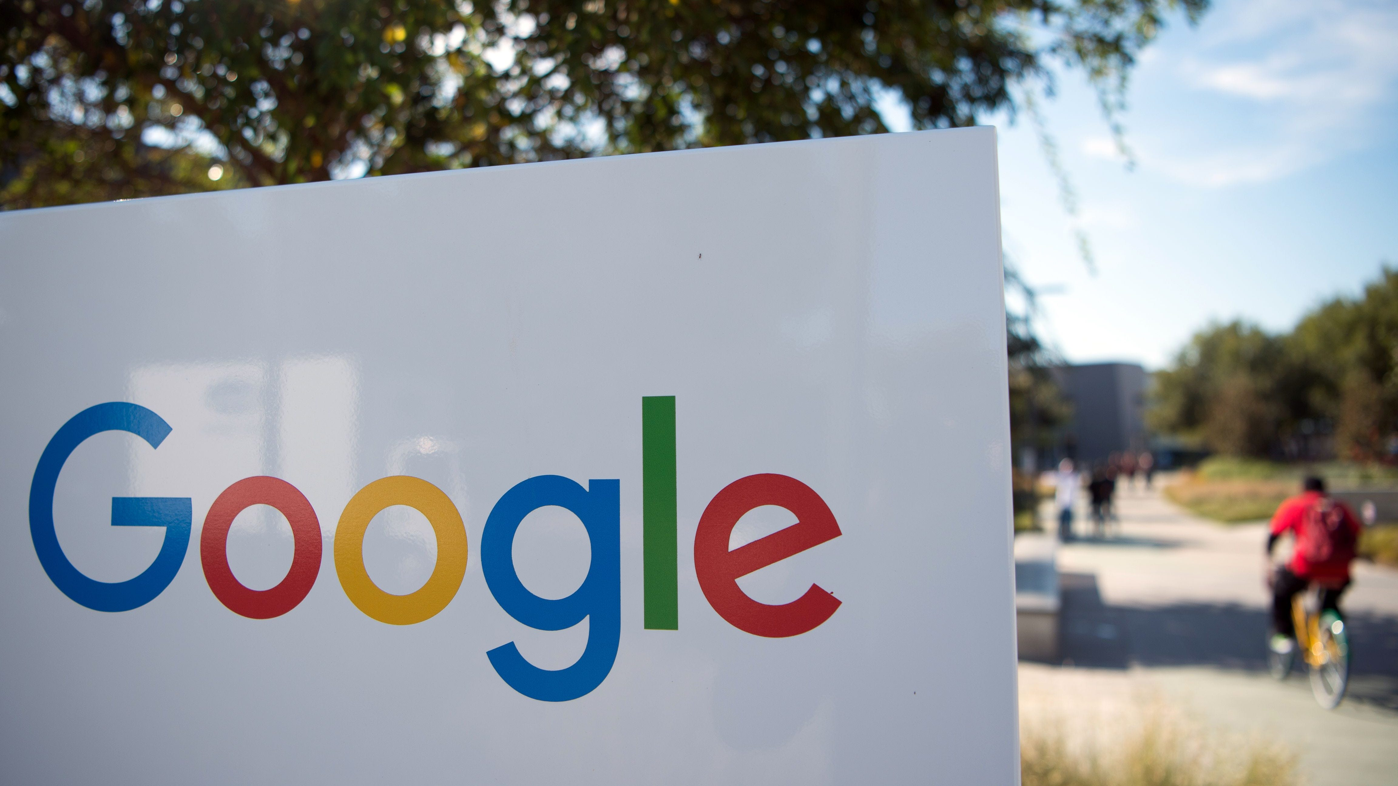 This file photo taken on November 4, 2016 shows a man riding a bike past a Google sign and logo at the Googleplex in Menlo Park, California.