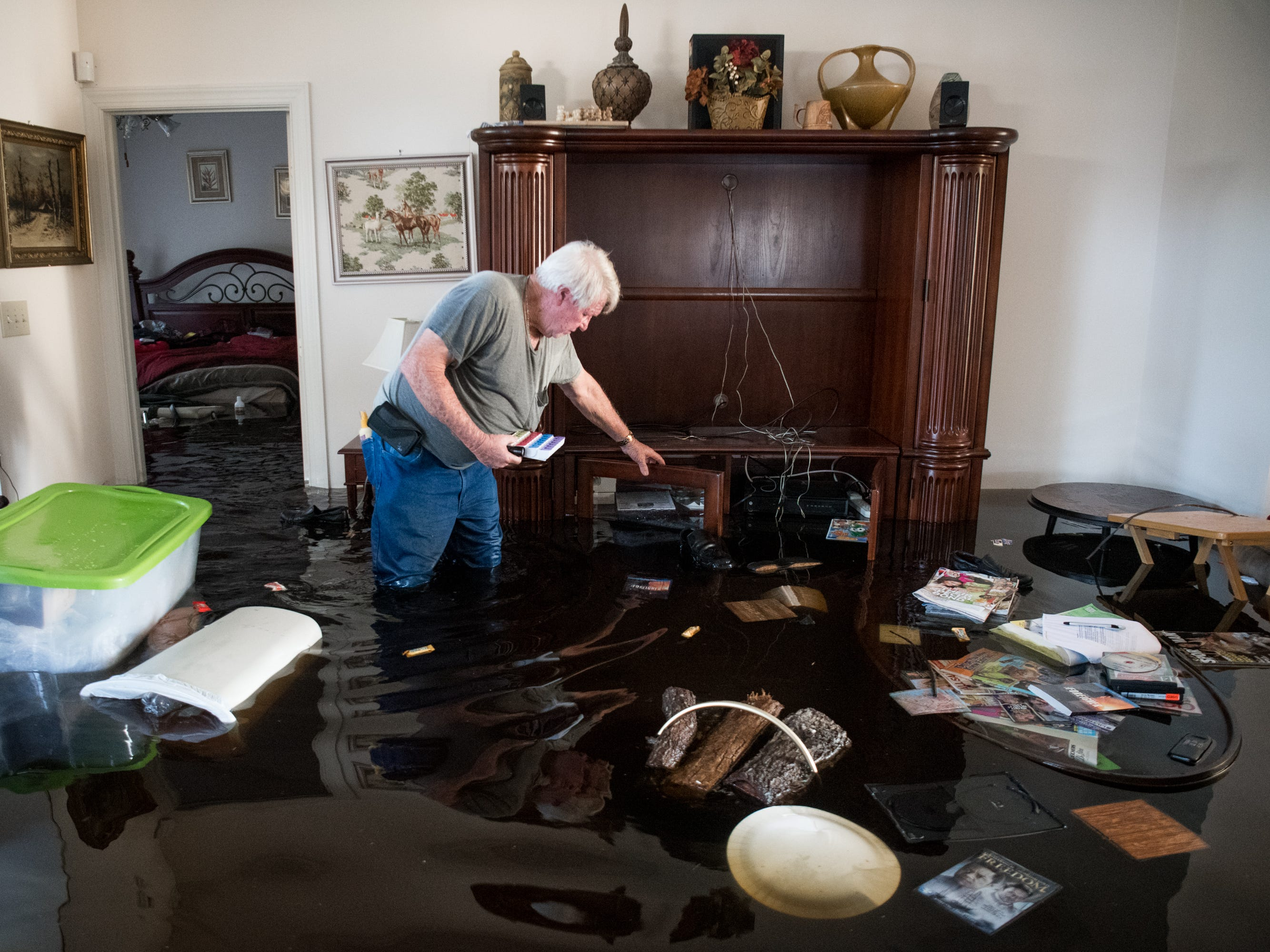 Billy Hardee removes valuables from his home as floodwater caused by Hurricane Florence rises at Aberdeen Country Club on Sept. 20, 2018, in Longs, S.C. Floodwaters are expected to rise through the weekend in the area.