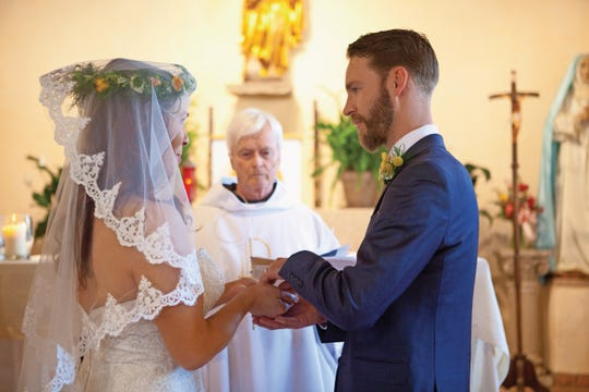 Felicia and TJ Parker pass arras back and forth during their wedding ceremony, which represents that they trust each other with finances.