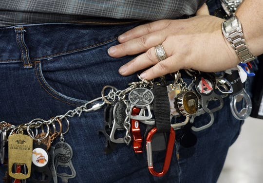 Kyra Selvidge of Denver shows off her collection of bottle openers during the Great American Beer Festival.