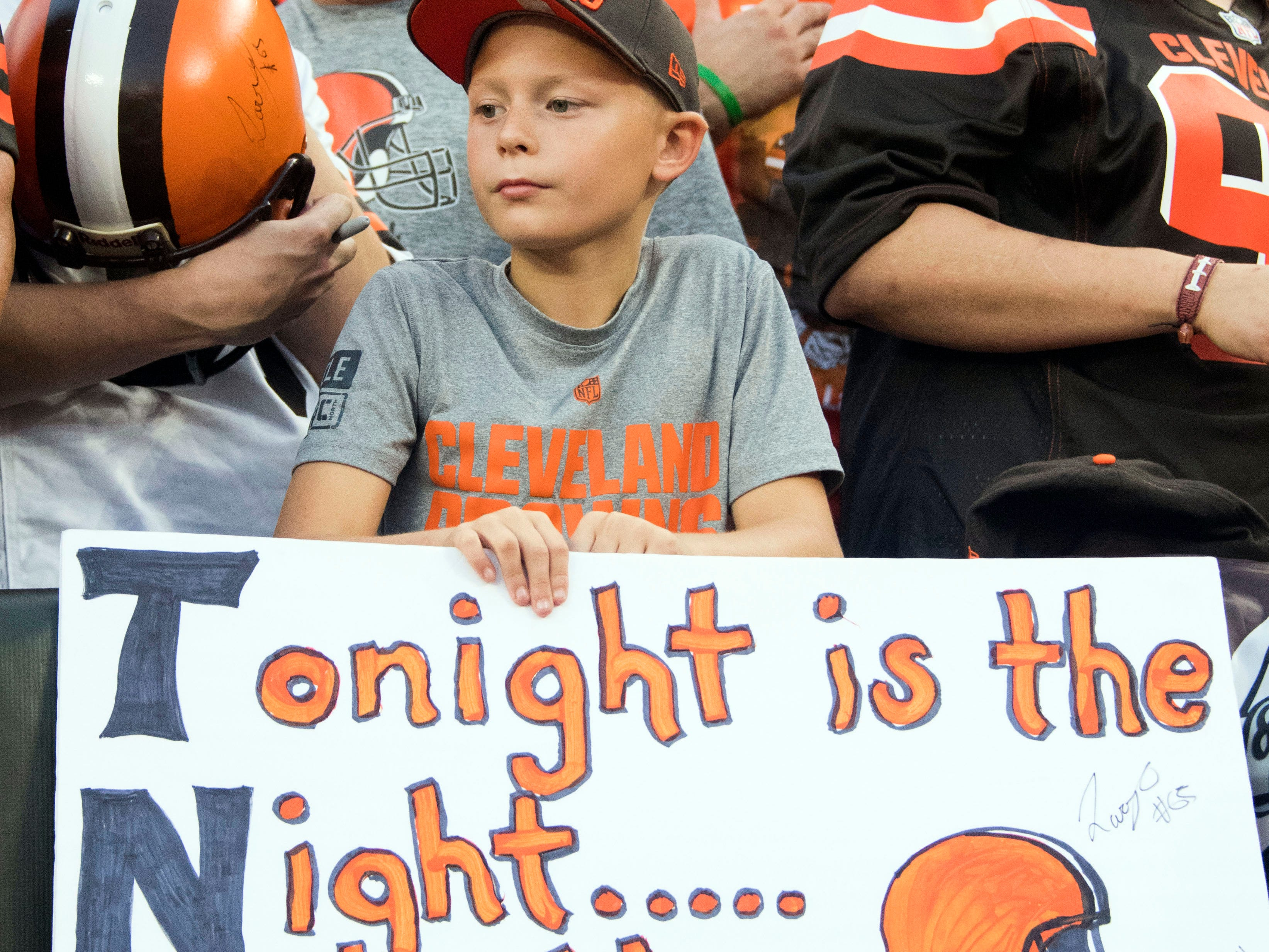 A young Cleveland Browns fan holds a sign referencing the Browns' winless streak and Thursday Night Football before the game between the Cleveland Browns and the New York Jets at FirstEnergy Stadium.