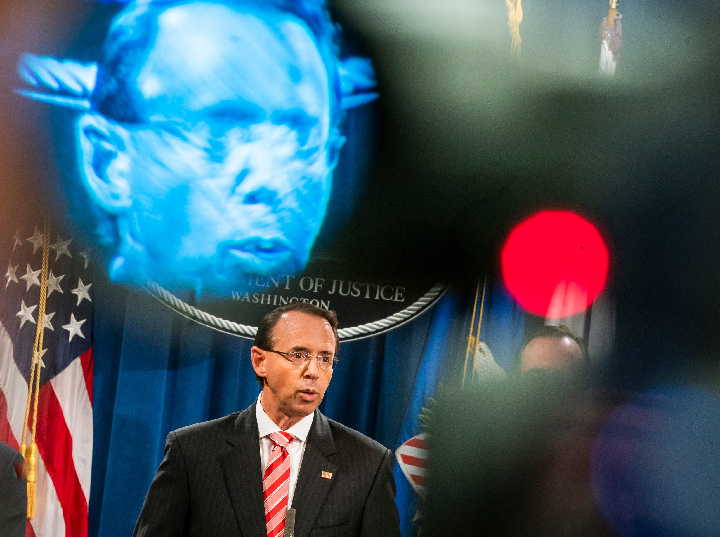 Deputy Attorney General Rod Rosenstein is seen in the viewfinder of a television camera as he announces that the Justice Department is indicting 12 Russian military officers for hacking Democratic emails during the 2016 presidential election at the Justice Department.. The Russians involved were working for the military intelligence service GRU, according to Rosenstein.