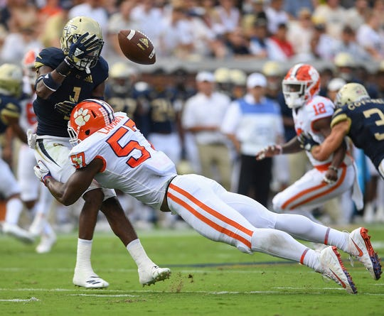 Clemson linebacker Tre Lamar (57) hits Georgia Tech A-back Qua Searcy (1) forcing a fumble during the first quarter.