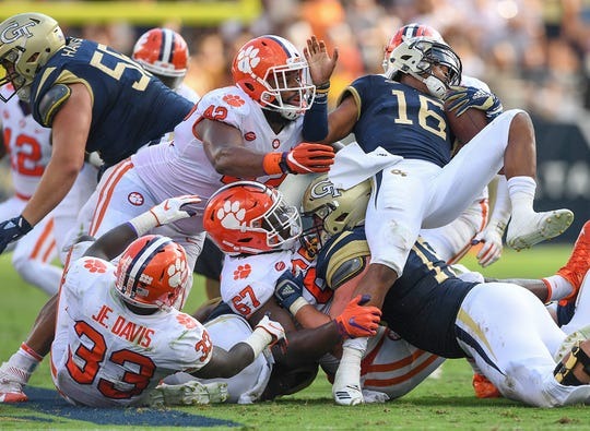 Clemson defensive lineman Albert Huggins (67) and defensive lineman Christian Wilkins (42) bring down Georgia Tech quarterback TaQuon Marshall (16).