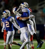 Appleton West High School's Bubba Thompson, left, congratulates Tyler Blake after Blake recovered a fumble in overtime against Appleton East High School during their football game Friday, Sept. 21, 2018, at the Banta Bowl in Appleton, Wis. 