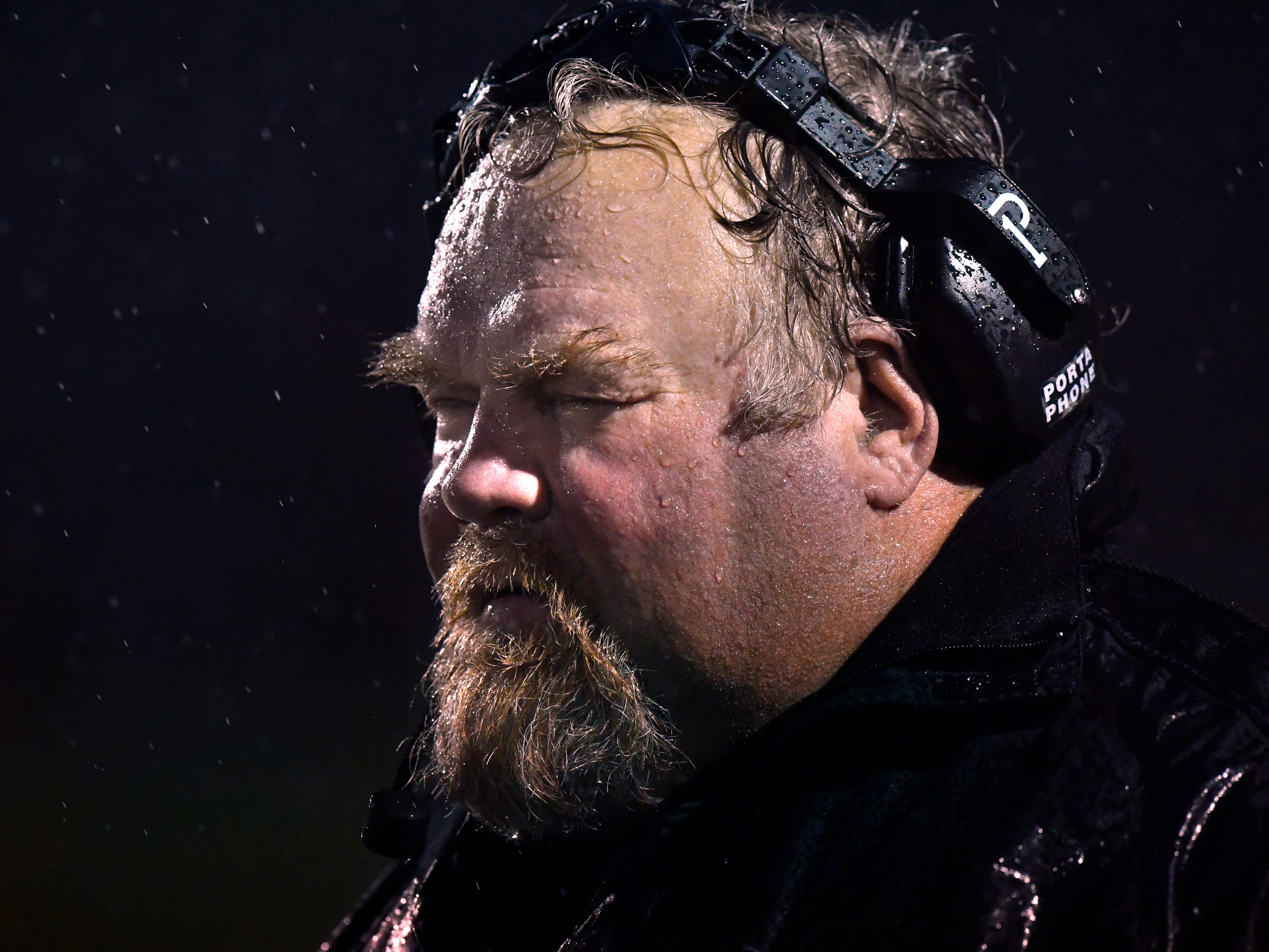 Abilene High assistant coach Wes Gorman blinks back the rain as he watches the game Friday Sept. 21, 2018 against Midland High. Weather was a factor in the game, leading to several turnovers, dropped footballs, and lost footing. Abilene won, 13-0.