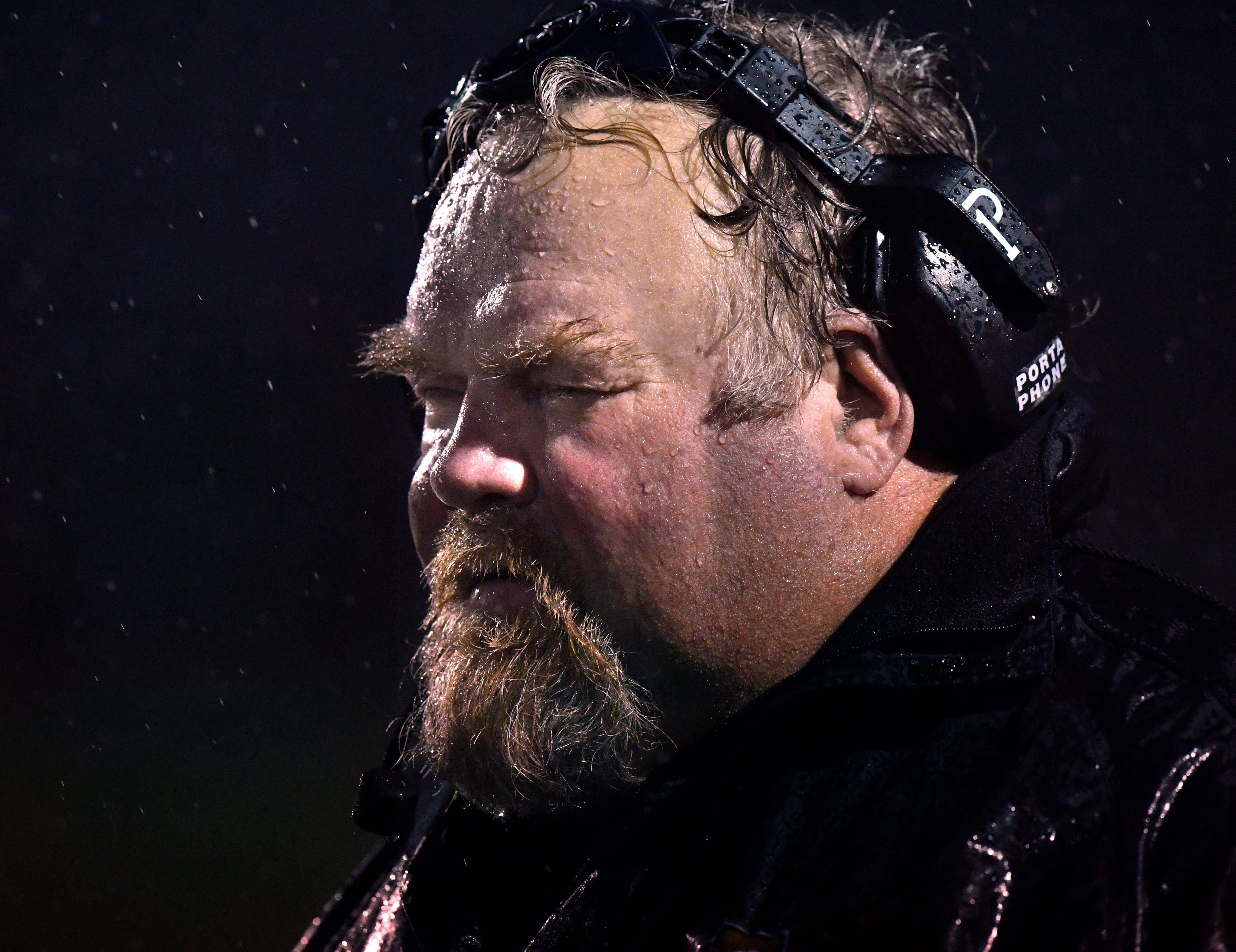 Abilene High assistant coach Wes Gorman blinks back the rain as he watches the game Friday. Weather was a factor in the game, leading to several turnovers, dropped footballs, and lost footing.
