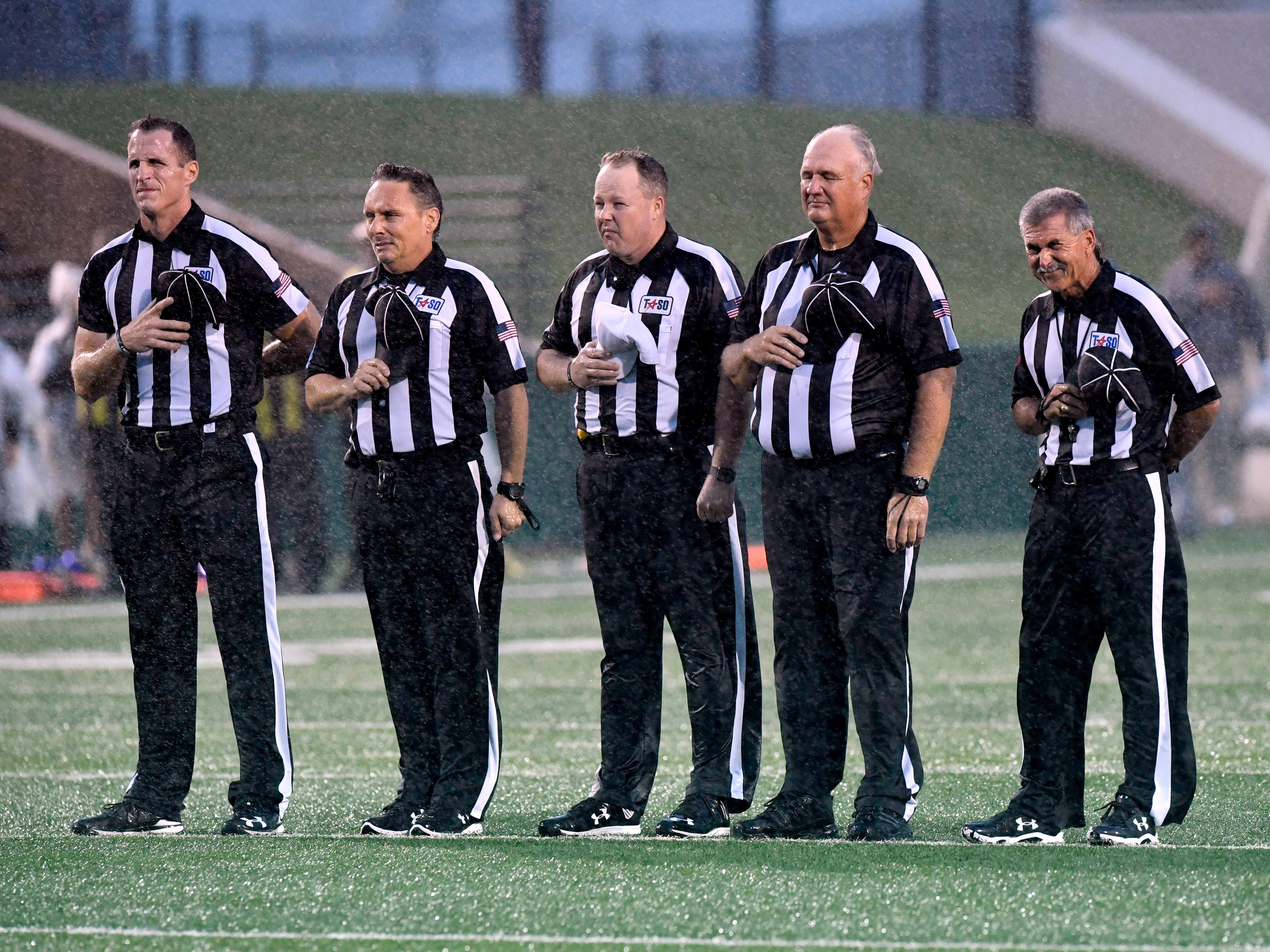 Game officials stand at attention in a driving rain for the playing of the National Anthem prior to the start of Abilene High's game against Midland High Friday Sept. 21, 2018. The rain and wind continued unabated through the night, at one point blowing back an Abilene High field goal attempt. Abilene won, 13-0.