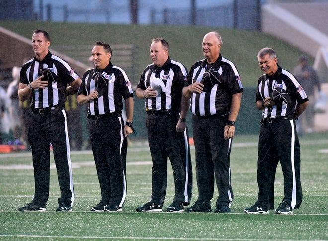 Game officials stand at attention in a driving rain for the playing of the national anthem prior to the start of Abilene High's game against Midland High on Sept. 21, 2018. The rain and wind continued unabated through the night, at one point blowing back an Abilene High field goal attempt.