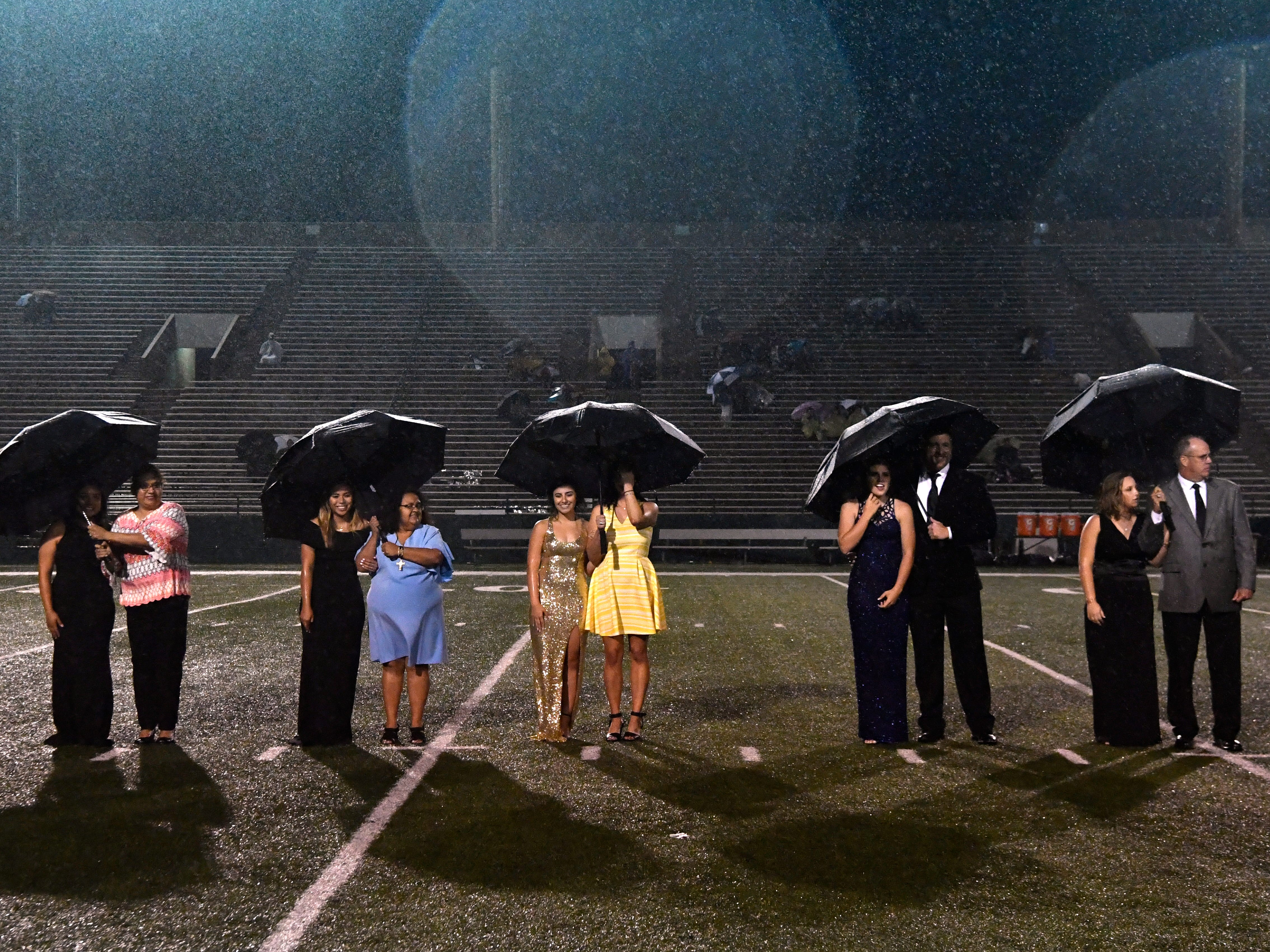 Candidates for Abilene High School homecoming queen wait in the rain for the announcement of who would be awarded the title Friday Sept. 21, 2018.