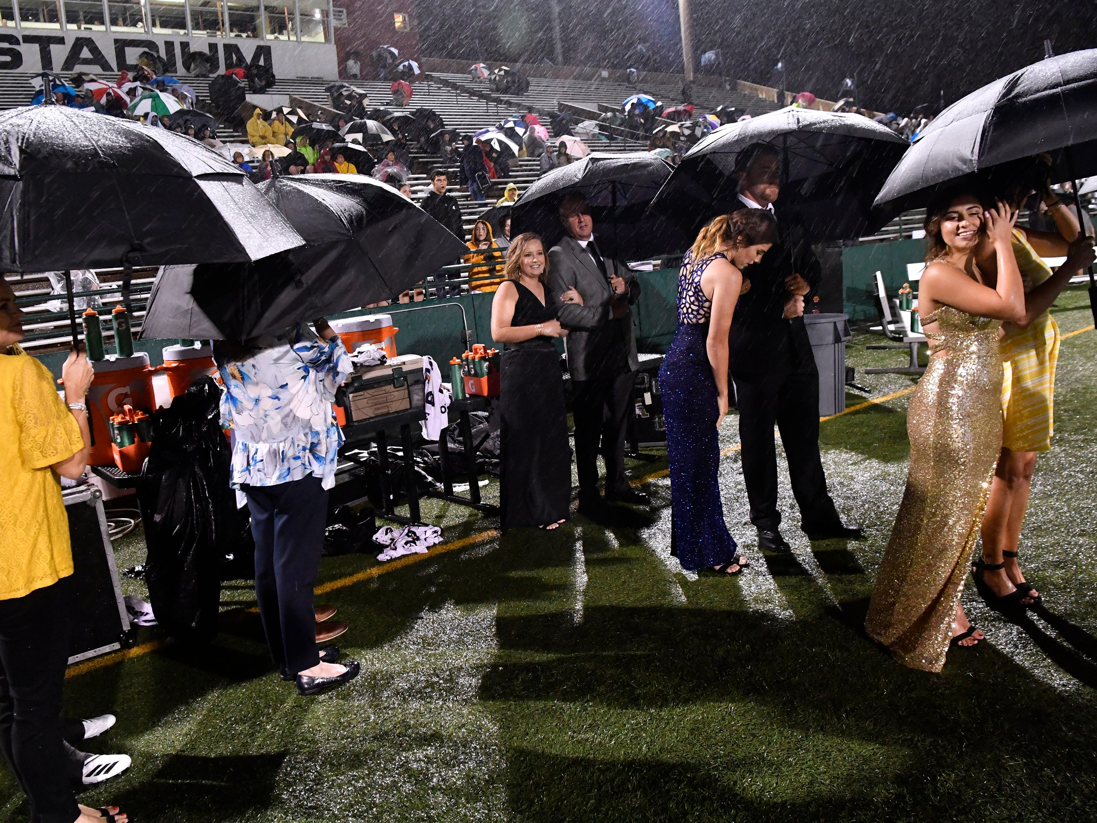 Members of the homecoming court and their escorts wait in the rain for the naming of the king and queen Friday Sept. 21, 2018.