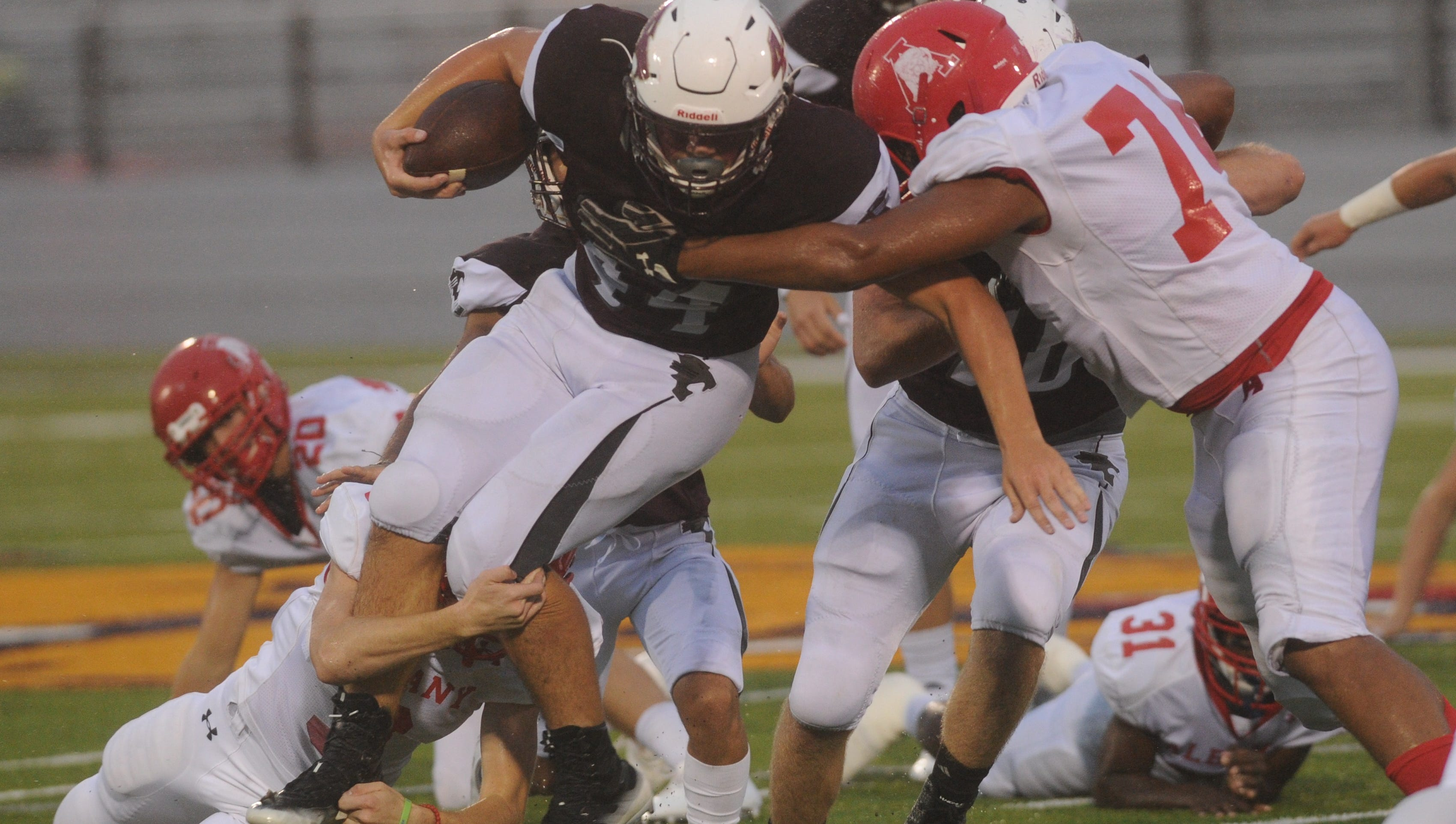 Hawley's Colton Marshall, center, carries the ball as Albany's Colby Knight, right, and another teammate try to bring Marshall down. Hawley won the game Friday, Sept. 21, 2018 at Wylie's Bulldog Stadium.
