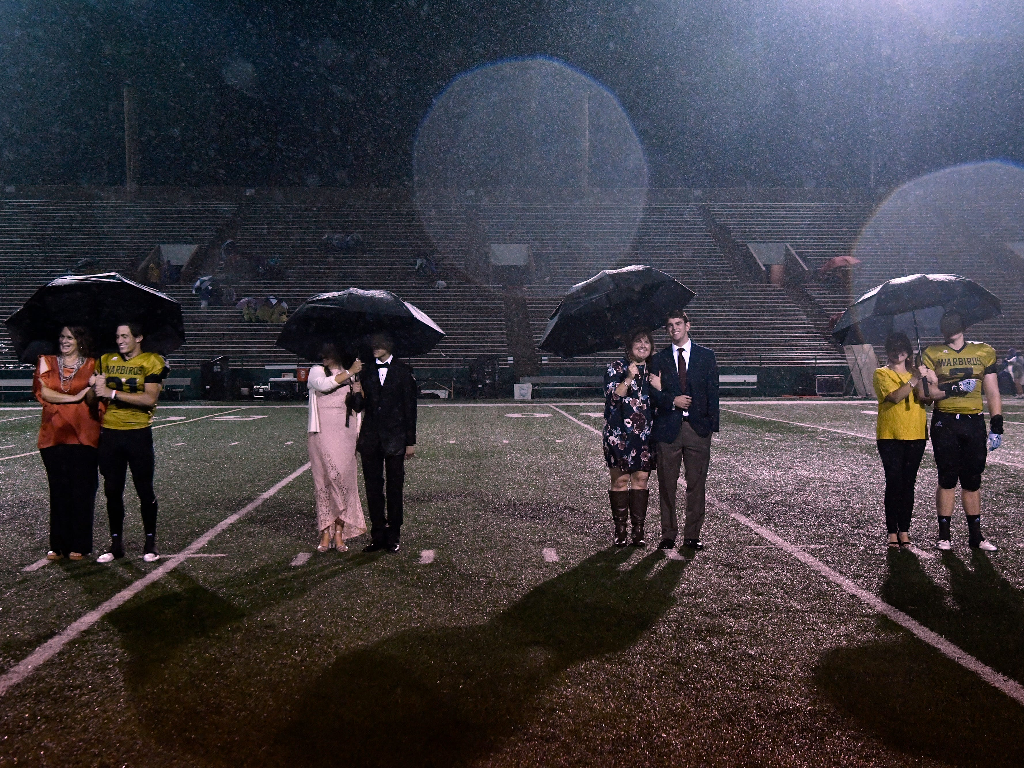 Candidates for Abilene High School homecoming king wait in the rain for the announcement of who would be awarded the title Friday Sept. 21, 2018.