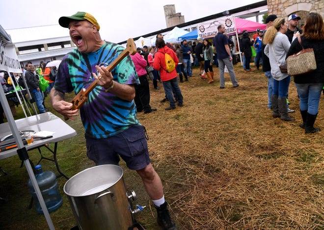 """Tom Bradley of the Big Country Homebrewers Association uses his mixing pad to play air guitar as Queen's """"Bohemian Rhapsody"""" plays over the loudspeaker at the Abilene Beer Summit Saturday. Bradley was making a beer called Barbecue Blonde from Texas Brewing, Inc. in Haltom City."""