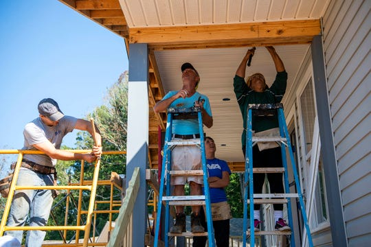 In this file photo, (from left) Asheville Area Habitat for Humanity executive director Andy Barnett, Habitat construction supervisor Kenny Busch, Rev. Dana Vaughn of Reems Creek-Beech Presbyterian and Interdenominational Ministerial Alliance president Rev. Damita Wilder work on siding and the porch of a Asheville Habitat home.