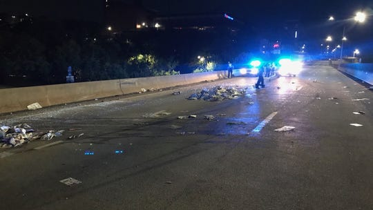First responders work to clean the mess left after a bad wreck on I-240 nearly claimed the lives of two Citizen Times delivery drivers.