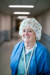 Mickey Donathan, certified registered nurse anesthetist at the Charles George VA Medical Center, stands in the hallway outside the operating wing on one of her last days at work.
