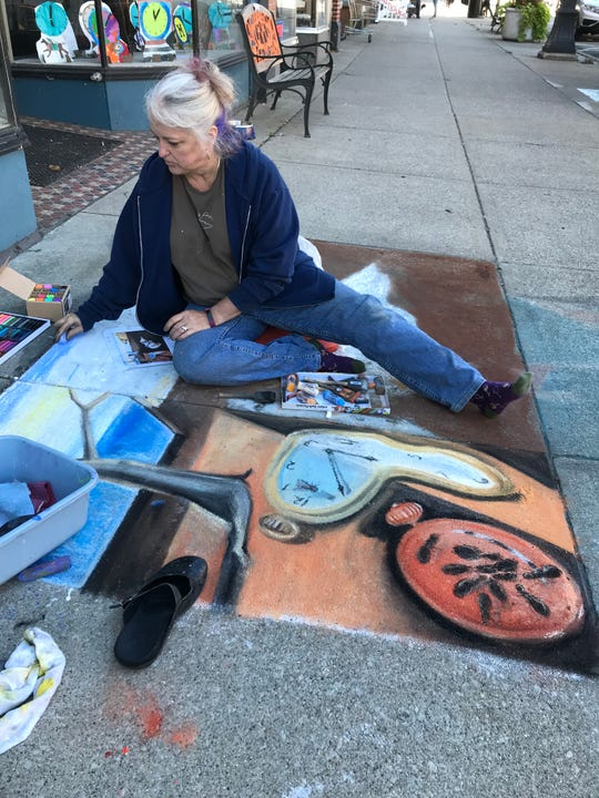 """Street artist Kat Whaley during a premiere weekend celebration of """"The House with a Clock in Its Walls,"""" in Marshall, Michigan - hometown of author John Bellairs"""