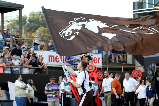 A Western Michigan cheerleader carries the flag onto the field at Waldo Stadium before the  Broncos game against Delaware State on Saturday, September 15, 2018.