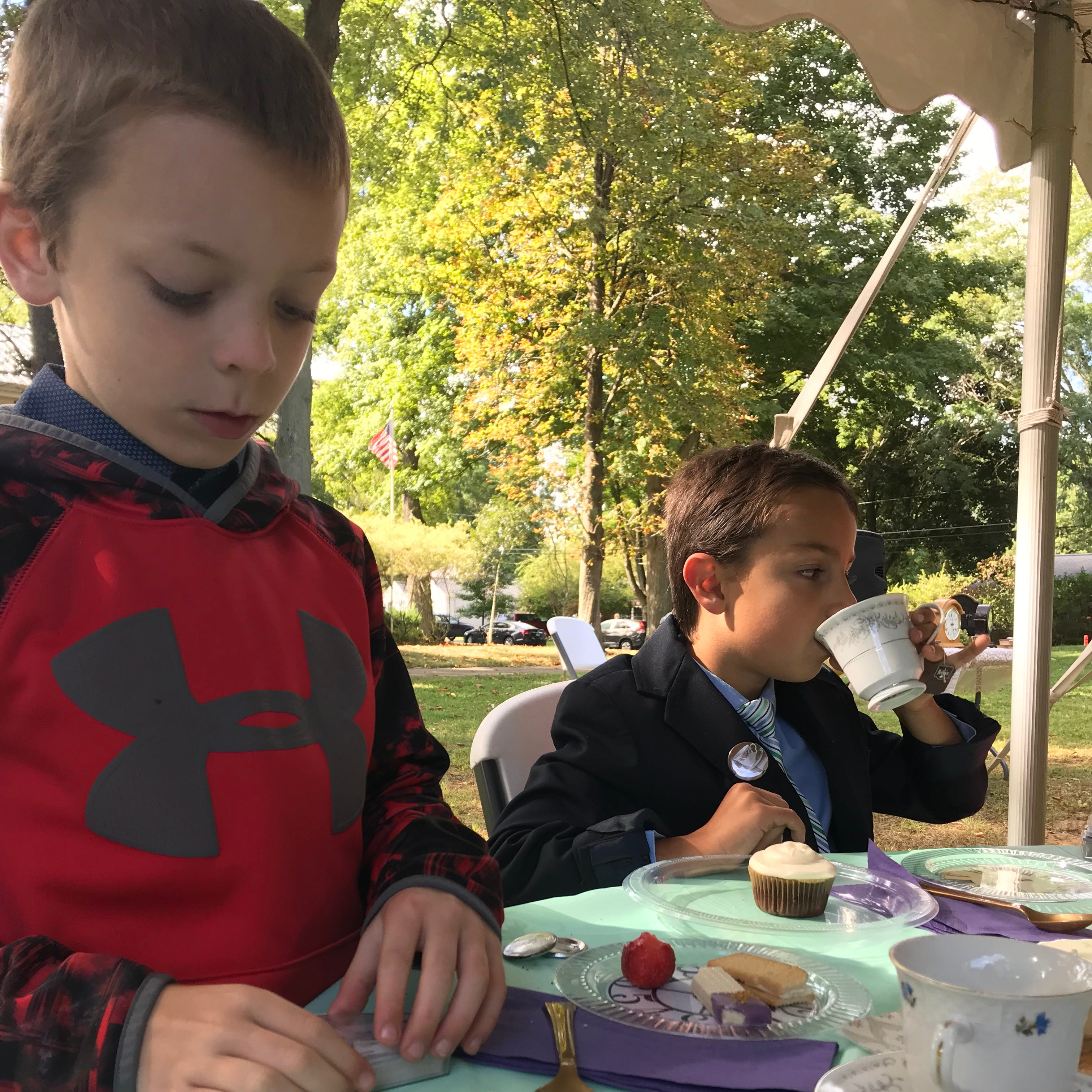 """Riley Adams, 8, and AJ Mathis, 8, drink tea and play with magic cards at a tea party to celebrate """"The House with a Clock in Its Walls."""""""
