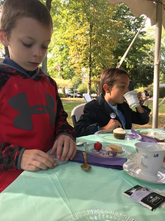 "Riley Adams, 8, and AJ Mathis, 8, drink tea and play with magic cards at a tea party to celebrate ""The House with a Clock in Its Walls."""