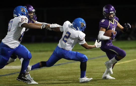 North Kitsap's John Jones tried to avoid a pair of Bremerton defenders during Friday's 49-0 win over Bremerton. Jones spent time at quarterback, running back and defensive back against the Knights.