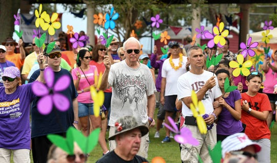 Hundreds of Brevardians hold up their flowers in recognition of someone they know suffering from Alzheimer's disease during Saturday's Walk to End Alzheimer's in Cocoa Village.