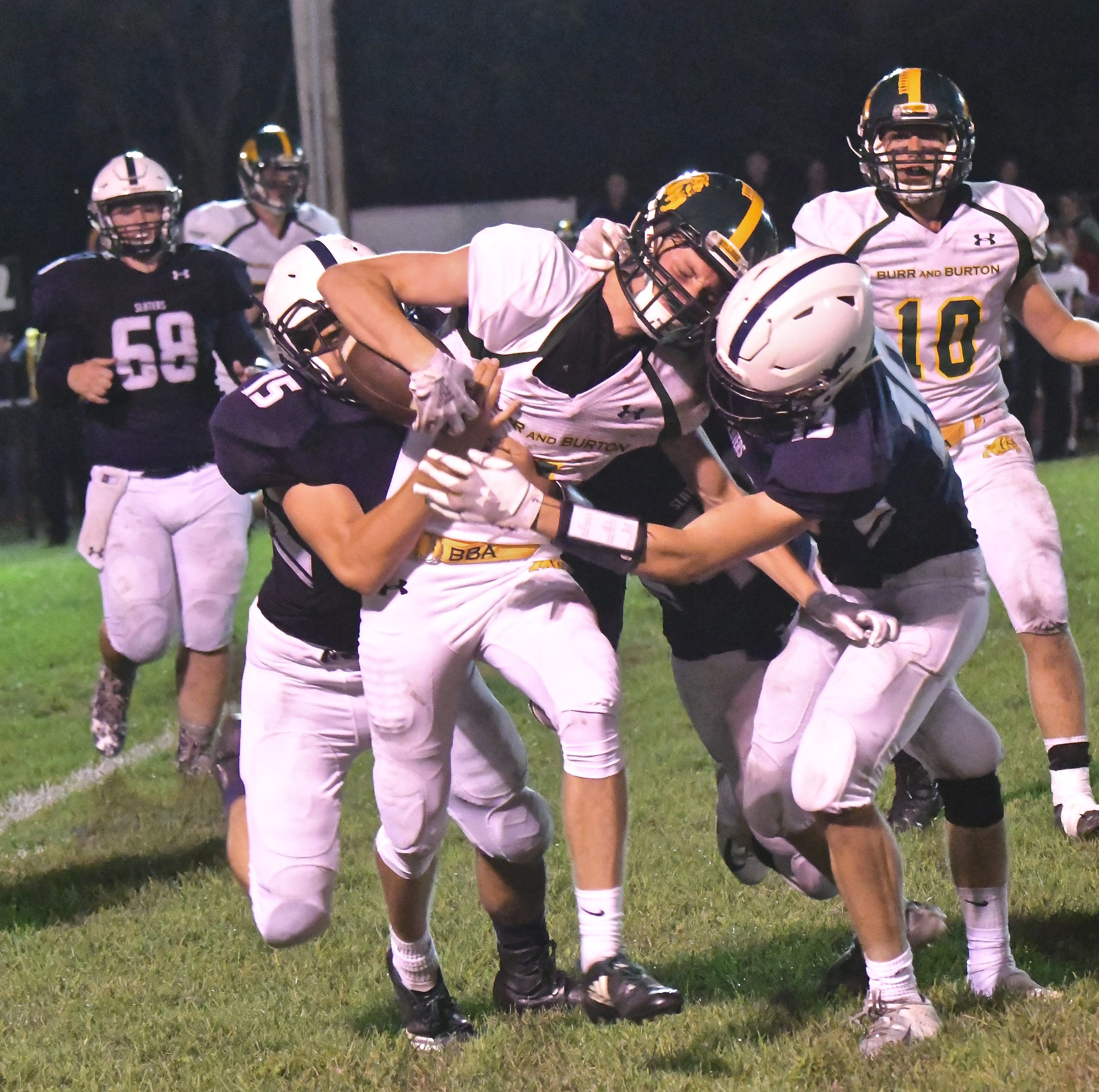 Burr and Burton's Jake Nicholson, center, is brought down by Fair Haven's Doug Hendee (15) and Brett Huntley (19) in the first half on Friday evening at Fair Haven Union High School.