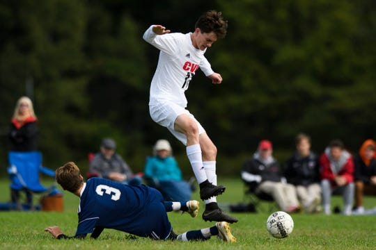 CVU's Nathaniel Sampson (17) leaps over the the sliding tackle by Essex's Stefan Digangi (3) during the boys soccer game between the Champlain Valley Union Redhawks and the Essex Hornets at Essex High School on Saturday morning September 22, 2018 in Essex. (BRIAN JENKINS/for the FREE PRESS)