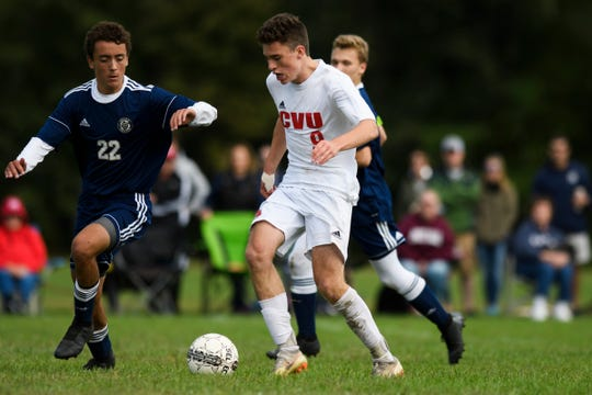 CVU's Jonah Roberts (9) runs with the ball past Essex's Dominic Minadeo (22) during the boys soccer game between the Champlain Valley Union Redhawks and the Essex Hornets at Essex High School on Saturday morning September 22, 2018 in Essex. (BRIAN JENKINS/for the FREE PRESS)