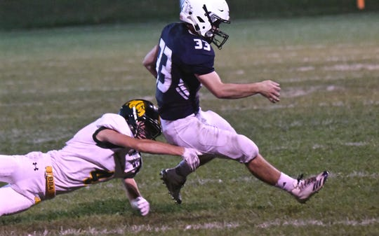 Fair Haven's senior running back Aaron Szabo (33) eludes a tackle from Burr and Burton Academy's Jake Nicholson (4) in the first half at Fair Haven Union High School on Friday evening.