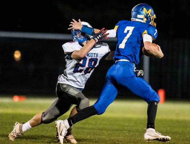 Milton's #7 Jacob Laware shoves off Mt. Anthony's #28 Chris Nolan during their high school football game in Milton on Friday, September 21, 2018.