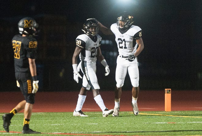 Burlington Township's Justin Johnson is congratulated by teammate Semi Robertson, right, after Johnson scored a touchdown during the first quarter of Friday night's football game between Burlington Township and Moorestown, played at Moorestown High School on September 21, 2018.