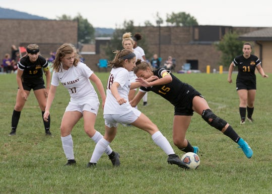New Albany's Ashley Clinger charges into Unioto's captain Kylee Bethel as they battle for possession of  the soccer ball Saturday afternoon at Unioto High School.