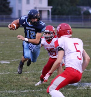 Adena quarterback Preston Sykes leaps past a Westfall defender.