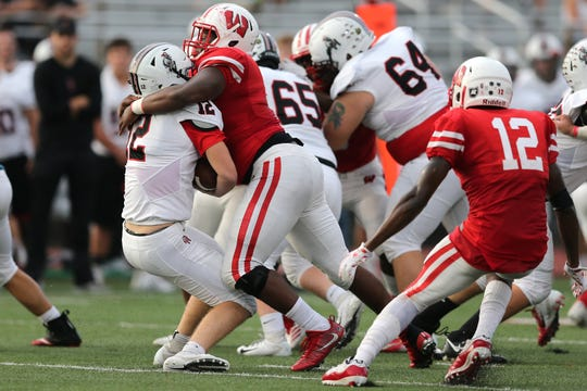 Lakota West Firebirds defensive tackle Ladonnis Griffin (52) tackles Oak Hills Highlanders running back Grant Rembold (12) for a loss in the first quarter during a high school football game between the Oak Hills Highlanders and Lakota West Firebirds, Friday, Sept. 21, 2018, at Lakota West High School in West Chester Township, Ohio.